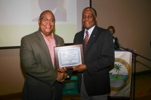 Grand Bahama Chamber of Commerce (GBCC) President Kevin D. Seymour (left) presents Dr Marcus Bethel with a plaque in appreciation of his presentation on the Hawksbill Creek Agreement Review Committee's recommendations during the GBCC's monthly meeting. (Photo: Keen i Media Ltd.)